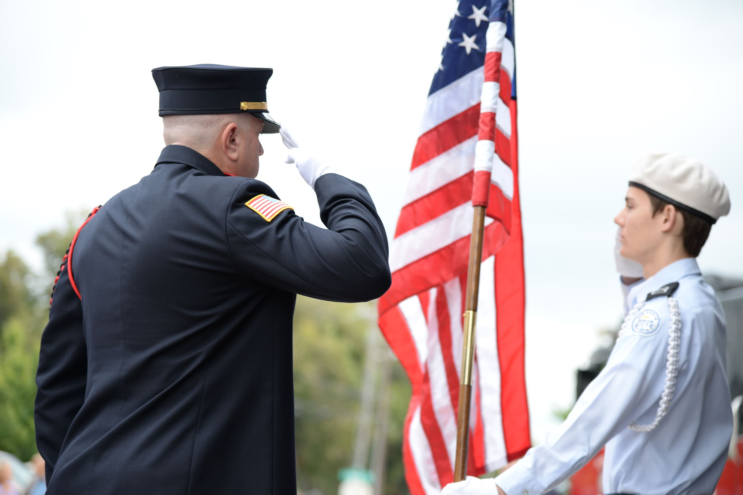 officer and boy scout salute American flag