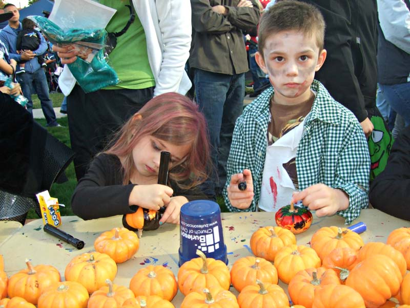 photo of kids decorating pumpkins